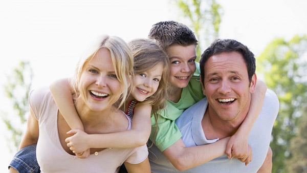 otac i majka sa dečakom i devojčicom se smeju ka kameri
