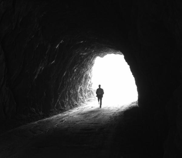 čovek na ulazu u mračnu pećinu iza kojeg je svetlost pred izborom