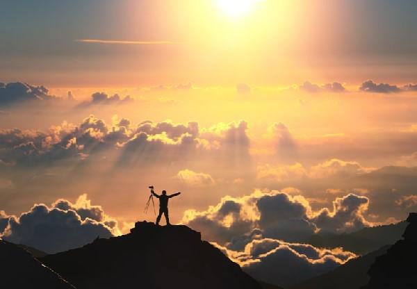 fotograf na vrhu planine među oblacima obasjan suncem