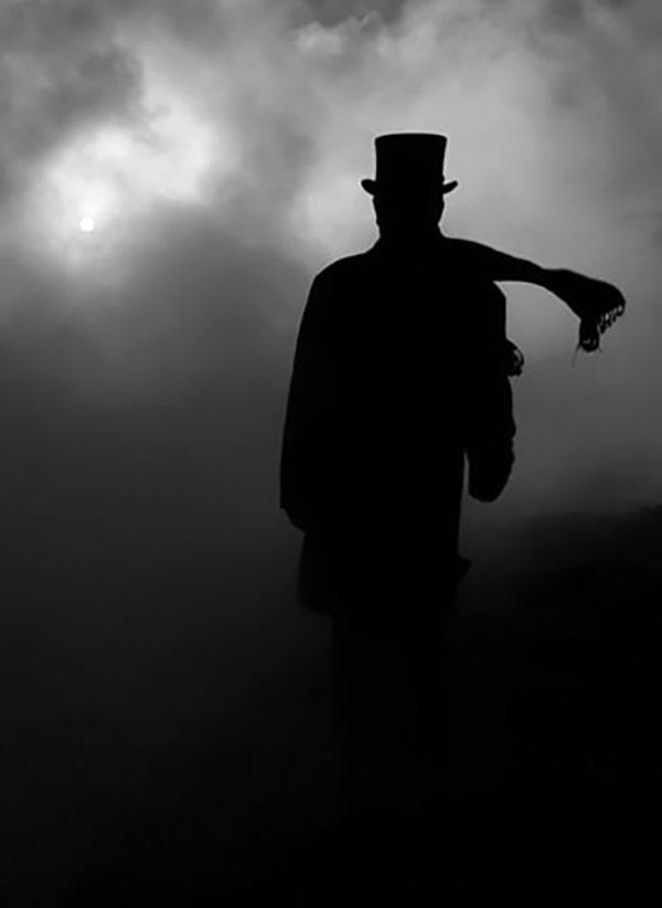 mračna silueta psihopate sa šeširom i šalom u magli